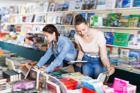 Positive woman with girl buying books in bookstore