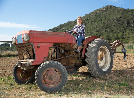 Skilled young woman driving small farm tractor, tilling soil on her vegetable garden