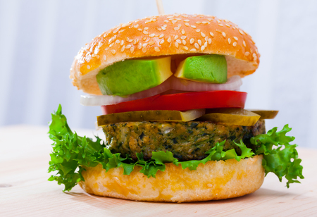 Delicious vegetarian hamburger with soybean patty, fresh vegetables and avocado  at plate