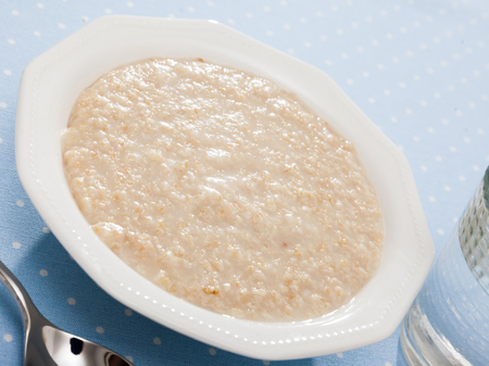 Boiled oatmeal porridge served in white plate. Concept of diet food 스톡 콘텐츠