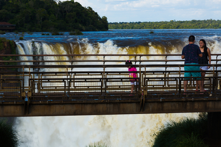 IGUAZU, ARGENTINA – FEBRUARY 16, 2017:  Tourists enjoying breathtaking view on the grand Iguazu Falls. Iguazu, Argentina Banque d'images - 124827666