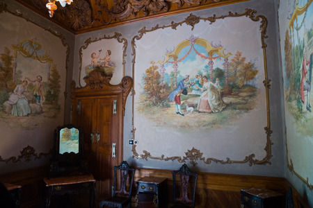 SINTRA, PORTUGAL - APRIL 21, 2019: Old frescoes, carved ceiling and antique furniture in interior of Palace in Quinta da Regaleira