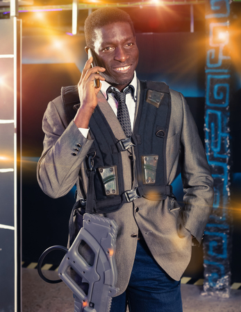 Portrait of African American man in business suit talking on mobile phone at laser tag room