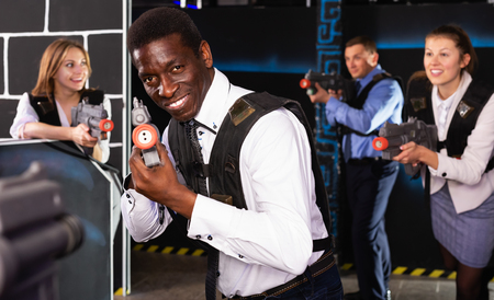 Portrait of Afro businessman playing laser tag with his co-workers on dark arena Imagens