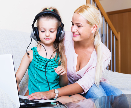Adult nanny and girl with headset playing computer game at home. Focus on girl Stock Photo