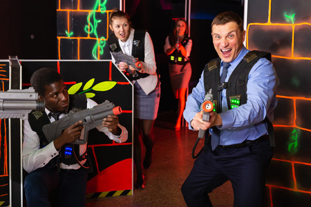 Emotional portrait of adult  men and women co-workers having corporate entertainment in laser tag room
