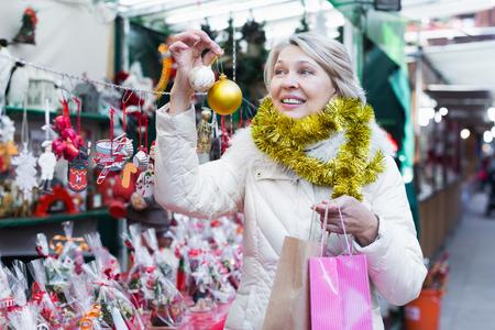 Portret van gelukkige rijpe vrouw in klatergoud met Kerstmisspeelgoed bij eerlijke openlucht Stockfoto