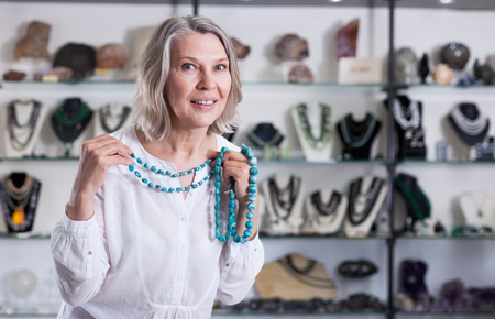 Woman trying on a turquoise necklace and earrings at a jewelry store