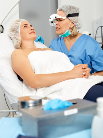 Doctor is examining woman patient before the procedure Stock Photo