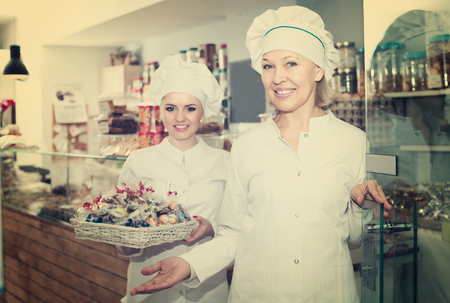 Smiling chefs with hats meeting customers at door in pastry shop Stock fotó