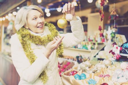 Smiling woman choosing Christmas toys at Christmas market  and walking