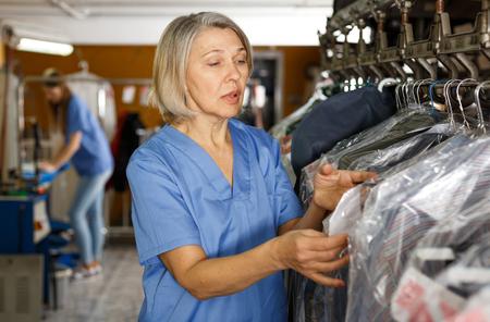 Portret wesołej pracowniczki pralni w jej miejscu pracy