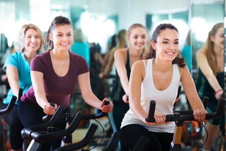 Mujeres felices positivas de diferentes edades entrenando en bicicletas estáticas juntas Foto de archivo