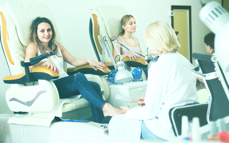 happy  clients doing toenails in nail salon in afternoon Imagens