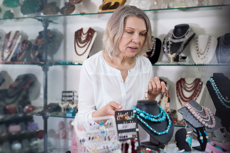 Seller of jewelry store lays the necklaces on the showcase Stock Photo