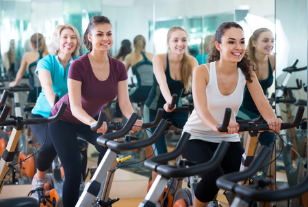 Brunette smiling european girl and other females working out in sport club