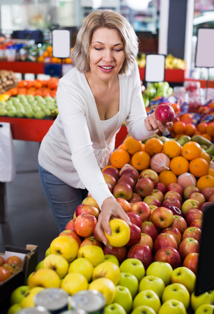 Portrait of smiling woman offering fruits in grocery