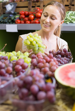 Charming young female seller wearing apron holding bunch of grapes on market