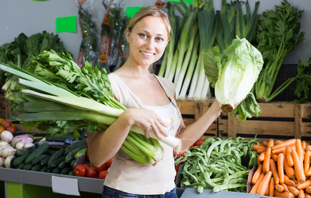 cheerful young female customer holding fresh celery and leek on market Stok Fotoğraf