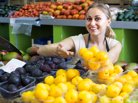 positive female in apron holding ripe plums in hands in fruit store Stok Fotoğraf