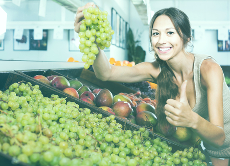 Young woman customer buying fresh ripe grapes on fruit shop
