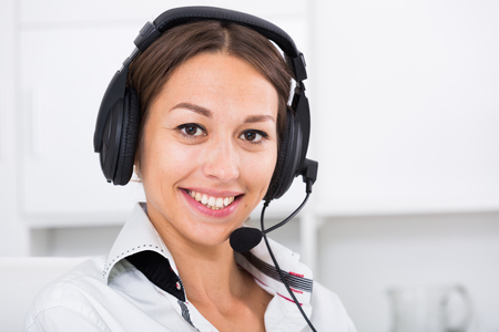 Mujer positiva hablando con el cliente mediante manos libres en el centro de llamadas Foto de archivo