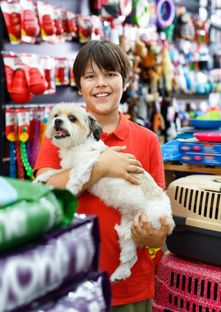 Smiling glad  positive  tweenager boy embracing his puppy during family shopping in pet accessories shop Фото со стока