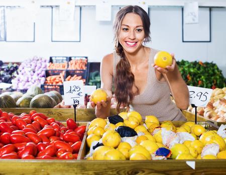 Positive young woman buying fresh lemons on marketplace