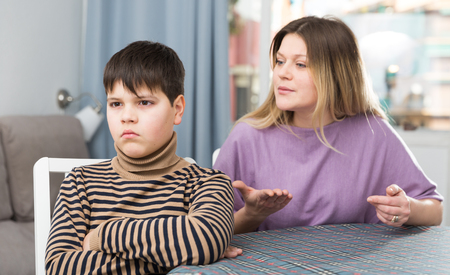 Upset mother and  offended son arguing in domestic interior Stock Photo