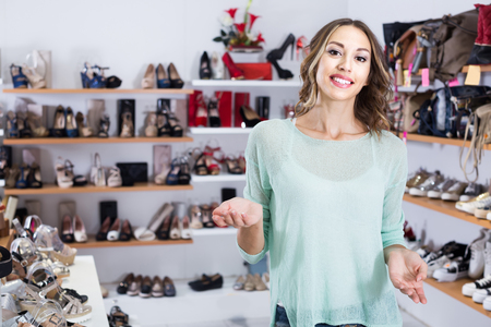 Portrait of young french  woman who is buying fashion footwear in boutique. Stock Photo
