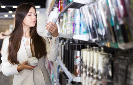Serious woman attentively looking haircare products at cosmetics shop