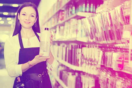 Portrait of professional young pleasant cheerful smiling woman hairdresser holding shampoo in shop