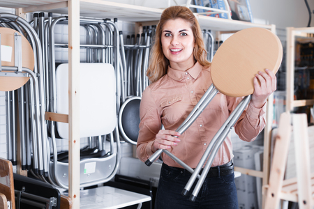 Smiling woman looking for new stylish tabouret for apartment in furniture salon Reklamní fotografie