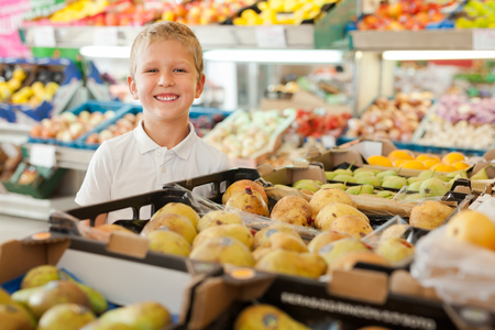 Portrait of cute cheerful kid at fruit and vegetable section of store