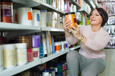 Positive charming woman choosing hair care products in shop and smiling