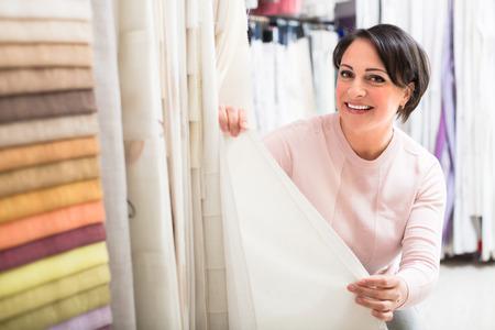 Smiling brunette choosing net fabric in  textile shop
