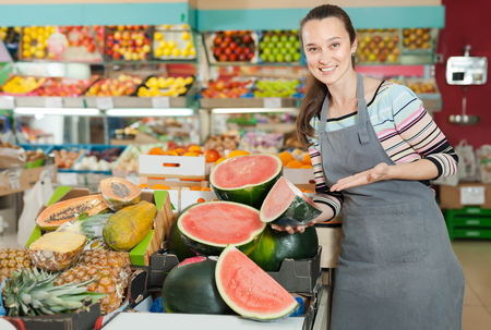 Smiling woman store worker in apron at fruit department of supermarket