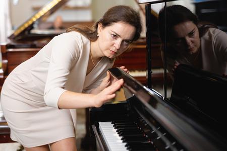 Junge Frau kauft ein Klavier in einem Musikgeschäft