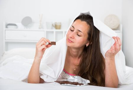 Adult woman secretly eating chocolate under sheets in bed