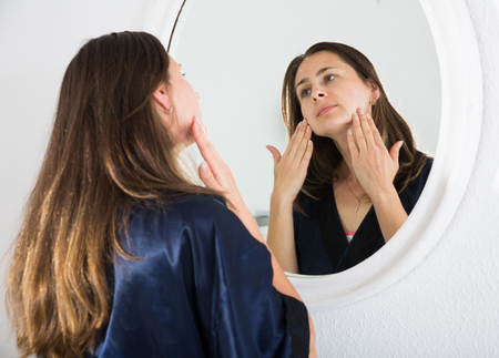 Young female touching face and looking at mirror in bedroom in sunny morning