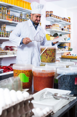 positive american shop staff standing near containers with olives in flavoured brine Stock Photo