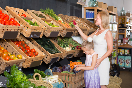 cheerful female customer with daughter holding vegetables in food shop