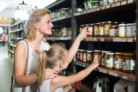 joyful female customer with little daughter choosing preserve tomato sauce in jar in food shop