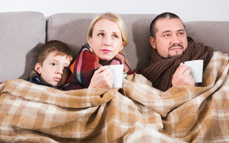 Ill family wrapping in blanket on couch at home drinking hot tea Banco de Imagens