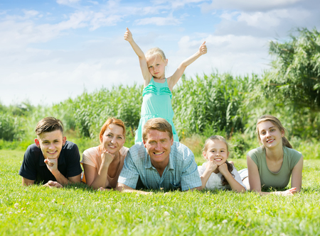 Portrait of happy large family of six lying together on green lawn outdoors