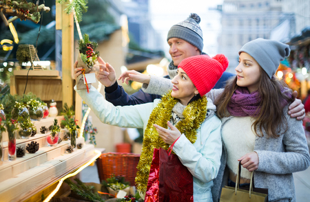 positive family of three with teenage girl choosing  floral decorations  at market. Shallow depth of focus Stock Photo
