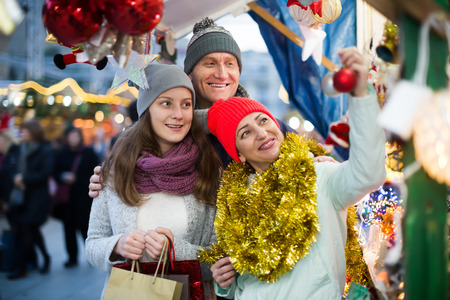 Portrait of ordinary family with teenager girl at  Christmas fair