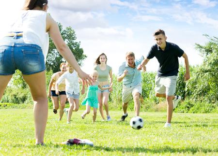 Genitori positivi con quattro bambini che giocano a calcio insieme sul campo verde il giorno d'estate