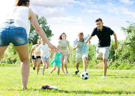 Positive parents with four kids playing soccer together on green field on summer day