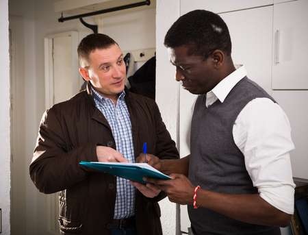 Two men with documents indoor having conflict about services offered